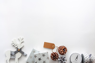 White gifts, reindeer and pine cones on the white copy space background. Empty space for text, flat lay, above view