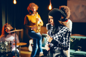 Band practice in home studio. Woman singing while rest of the band playing instruments.