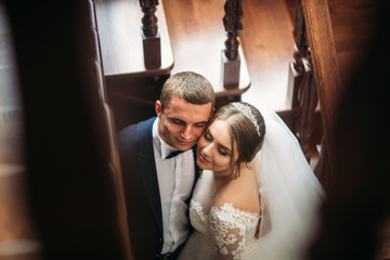 Groom and bride stand near the stairs. Couple close eyes