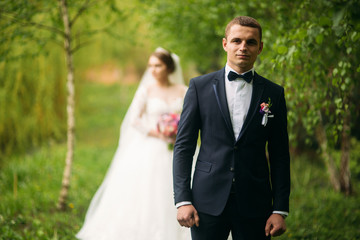 The newlyweds are walking in the park on the wedding day. The bride and groom Enjoying at the wedding day
