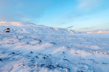 Layers of snow on a beautiful Winters day in Iceland. A tour bus is in the distance