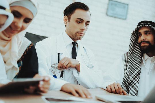 Arabic Patient Giving Dollars Money to Doctor.