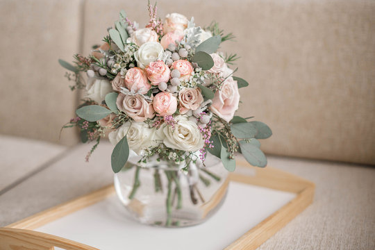 Wedding bouquet in shades of dusty rose, white, green, beige, pink and purple. Beautiful and delicate bridal bouquet in the glass vase.