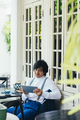 Elegant Asian businessman reading from his tablet at cafe.