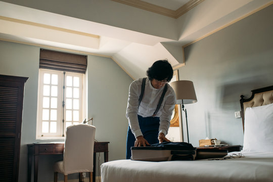 Asian man hotel guest packing his clothes in suitcase.