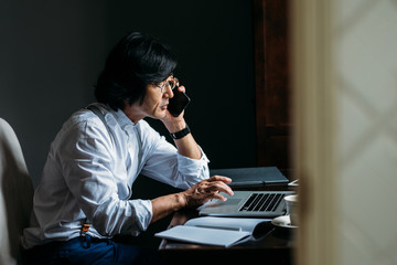 Serious middle-aged Asian businessman working at his office and talking on his cell phone.