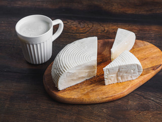 Slices round homemade goat cheese on the wooden board