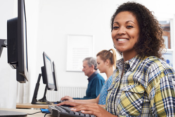 Portrait Of Young Woman Attending Computer Class In Front Of Screen