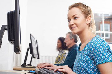 Young Woman Attending Computer Class In Front Of Screen