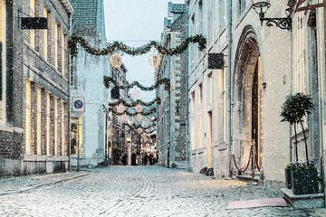 Shopping street with christmas lights and snowfall in the Dutch city of Maastricht