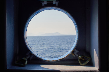 View though a ship window porthole of a traveling ferry onto the aegean sea with a small island on the horizon.