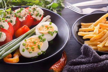 Half boiled eggs with tomatoes, green onions, sprinkled with greens in a black plate on a gray wooden table. Close-up