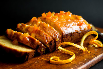 Close up of sliced orange marmalade cake on wooden cutting board
