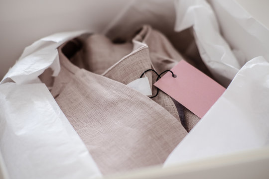 White opened box with wrapping paper and pink linen cloth and label. Copyspace for text