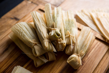 Close up of  wrapped tamales on cutting board