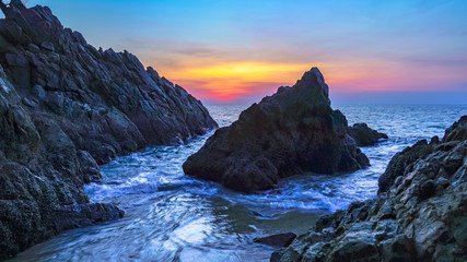 waves hit the big cone shape rock in the middle of stone cape during sunset at banana beach Phuket