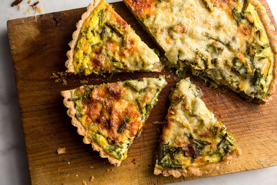 Close up of roasted asparagus and scallion quiche slices on cutting board