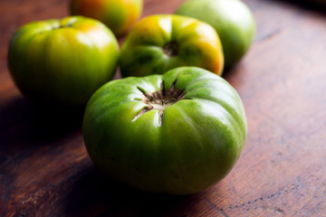Close up of green tomatoes on wooden table