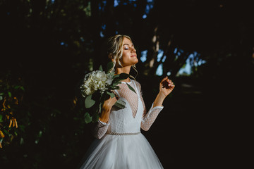 A girl in the white dress of the bride makes a photo in the park.