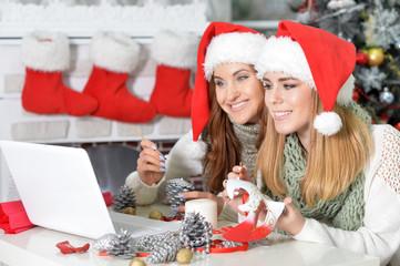 Portrait of women in Santa hats using laptop