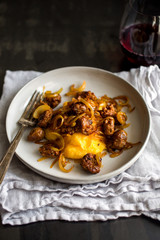 Close up of squash polenta with sausage and onion served on plate