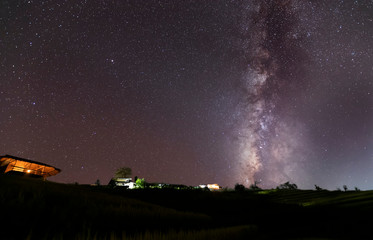 Milky Way Galaxy over hut on paddy rice field at night sky.