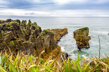 Sea and natural layered rock formations from erosion. Pancake Rocks and Blowholes, Paparoa National Park, West Coast, near Hokitika, New Zealand.