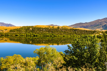 Peaceful and calm scene, relaxing hilly and lake landscape. Lake Hayes, Queenstown, New Zealand.