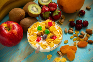 Tasty cornflakes with milk and fruits in glass bowl