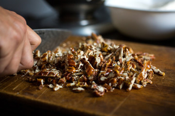 Close up of man's hand chopping pecans on wooden cutting board