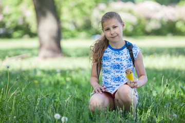 Preteen girl sitting in grass in park with sketchbook and pencil in hands, copy space
