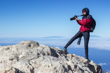 Photographer takes picture while standing on the mountain peak at strong wind