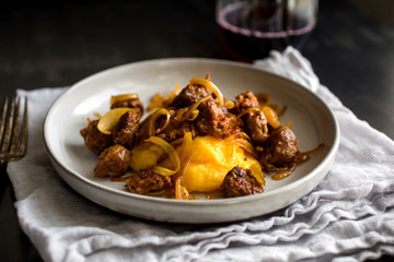 Close up of butternut squash polenta with sausage and onion served on plate