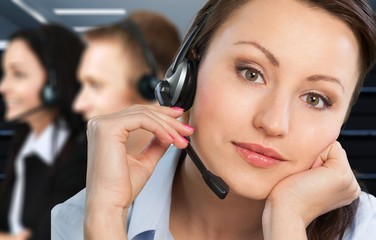 Female call center employee with coworkers on background