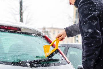 Young man in black coat cleans his car with yellow brush during snowfall. Winter inclement weather.