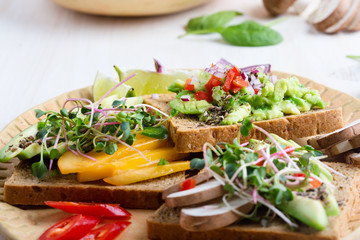 Selection of avocado toasts on grain bread. Healthy plant-based food