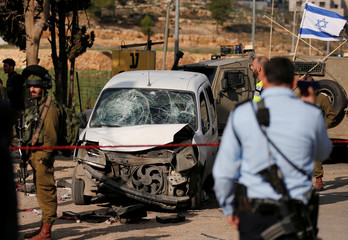 Israeli policemen inspect the scene of a car-ramming attack near Hebron, in the occupied West Bank