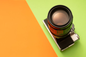 Photo camera on green and orange background
