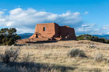 Ruins of an old adobe Spanish mission church in a grassy meadow in Pecos National Historical Park near Santa Fe, New Mexico