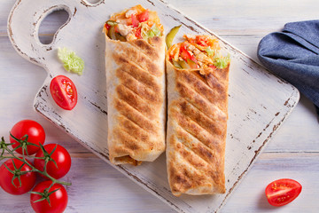 Chicken wraps with tomatoes, pickles, cabbage lettuce and onion. Tortilla, burritos, sandwiches, twisted rolls. overhead, horizontal