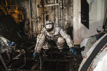 Accident in the engine room in the engine room on the tanker worker in a white protective chemical suit eliminate the problem.