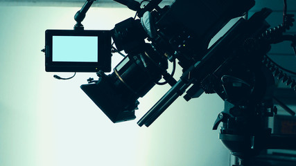 Silhouette images of video camera in tv commercial studio production which operating or shooting by cameraman and film crew team in set and prop on professional crane and tripod for pan tilt or shift