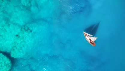 Yacht on the water surface from top view. Turquoise water background from top view. Summer seascape from air. Travel concept and idea Wall mural
