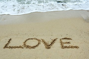 Love text on a sand beach with waves.