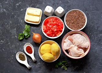 Ingredients for the preparation of chicken stew with lentils, potatoes and tomatoes: Chicken pieces, lentils, tomatoes, butter, peeled potatoes, onions, fresh basil, spices, salt, pepper. Top view.