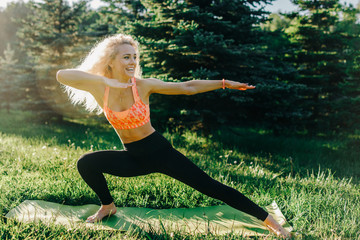 Image of young curly-haired sports woman practicing yoga on rug