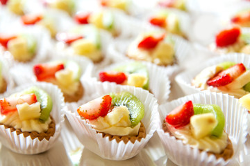 Close up of small sweet canapes arranged on a mirror plate over light background - selective focus