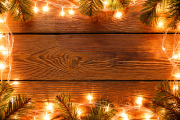 Image of wooden surface with burning garland around perimeter, branches of spruce.