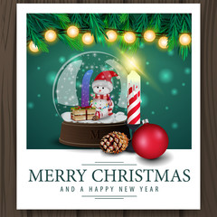 Photo with snow globe with snowman inside and merry Christmas greetings