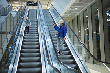Mother and child together on escalator background. Terminal, airport travel, love care.